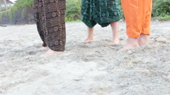 Guys in Indian national clothes run along sand beach one falls Stock Footage