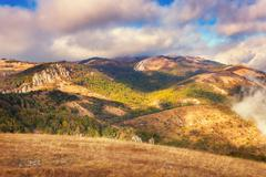 Dramatic mountain autumn landscape at sunset. Low clouds - stock photo