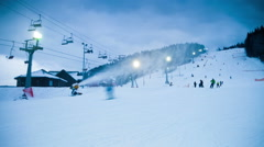 Night skiing at the ski slopes and snow cannons. Timelapse Stock Footage
