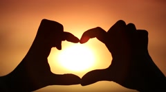 Silhouette of hand in heart shape with sun in the middle Stock Footage