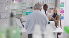 4K Team of staff working & serving customers in a chemist shop - stock footage