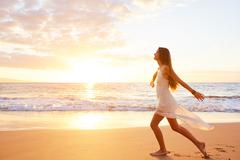 Happy Carefree Woman Dancing on the Beach at Sunset Stock Photos