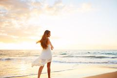 Happy Carefree Woman on the Beach at Sunset - stock photo