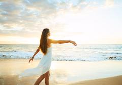 Happy Carefree Woman on the Beach at Sunset Stock Photos