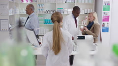 4K Team of staff working & serving customers in a chemist shop Stock Footage