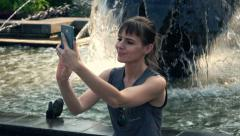 Woman taking photo with cellphone by fountain, super slow motion Stock Footage