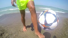 Man practices tricks with a football on beach SLOW MOTION - stock footage