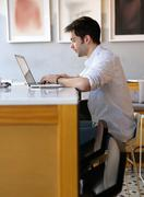 Young man typing on laptop at internet cafe - stock photo