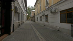 Woman walking on a narrow street in Baia Mare Stock Footage
