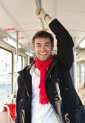 Stock Photo of Happy young man traveling with public transport