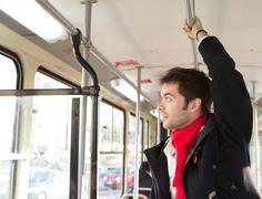Young man traveling by public transport - stock photo