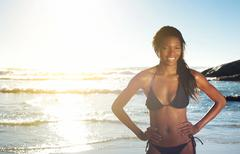 Young african american woman smiling at the beach Stock Photos