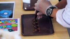 Close up of the confectioner-cook hands squeezes melted chocolate Stock Footage