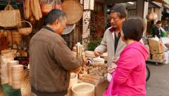 Basketry shop on street, full with hand made items, client give money to seller Stock Footage