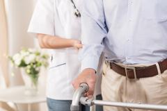 Nurse assisting an elderly man - stock photo