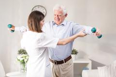 Nurse helping patient to exercise - stock photo