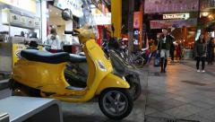 Yellow Vespa motorbike parked on night street. People walk on background Stock Footage
