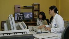 Female radiologist and technician performing medical exam in radiology lab. - stock footage