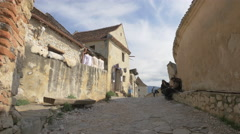 Sitting and walking on a lane with old buildings inside the Rasnov Citadel Stock Footage