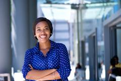 Happy young business woman standing outside office building - stock photo
