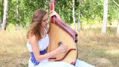 Girl playing the pandora in the grove Stock Footage