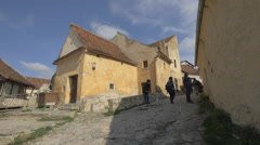 Walking on a lane with old houses at Rasnov Citadel Stock Footage