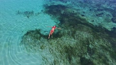 Young and beautiful fashion female model in red bikini lying on the waves in the Stock Footage