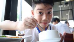 happy asian child eating soup at restaurant - stock footage