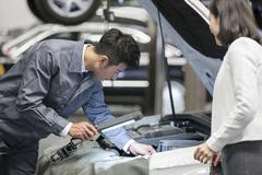 Auto mechanic talking with car owner Stock Photos