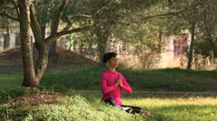 young woman practicing meditation in the park - stock footage