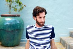 Fashionable male model in striped shirt sitting outdoors - stock photo