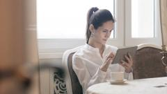 Woman using tablet and drinking coffee by table Stock Footage