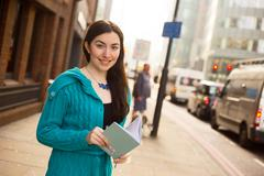 young girl in the street holding a book - stock photo