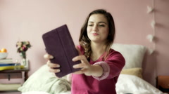 Teenage girl doing selfies on tablet while sitting on her bed Stock Footage