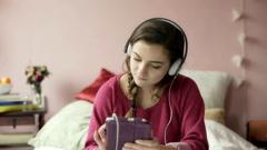 Teenage girl browsing internet on tablet and listening music on headphones Stock Footage