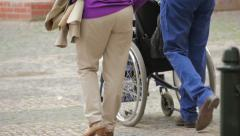 Family walking with woman in wheelchair, slow motion Stock Footage