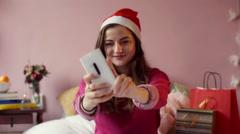 Teenage girl wearing Santas hat and doing selfie on smartphone Stock Footage