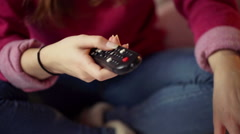 Girl sitting cross-legged and holding remote control in her hand - stock footage