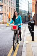 young woman riding a hire bike - stock photo