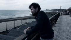 Sad lonely angry man in front of the ocean Stock Footage