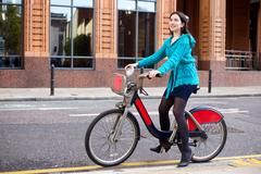 a young woman using a hire bike - stock photo