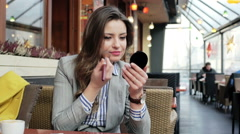 Businesswoman improving her makeup while sitting in the outdoor cafe Stock Footage