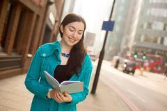 Young woman reading a textbook in the street Stock Photos
