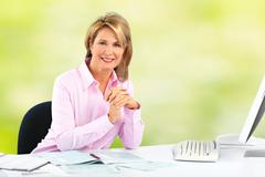 Smiling mature business woman. Green background - stock photo