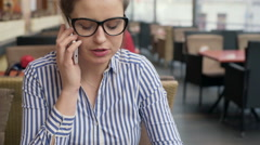 Businesswoman sitting in the cafe and talking on cellphone, stadycam shot Stock Footage