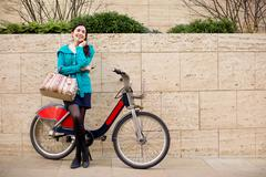 happy young woman in the street with a hire bike - stock photo