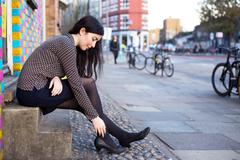 Young woman in the street feeling pain in her ankle Stock Photos