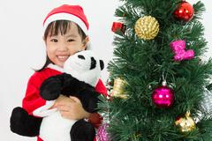 Asian Chinese little girl holding panda doll posing with Christmas Tree Stock Photos