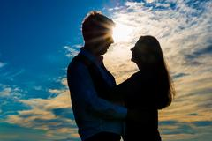 silhouette of a loving couple hugging at sunset - stock photo