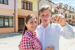 Man showing the key of the house and embracing his wife Stock Photos